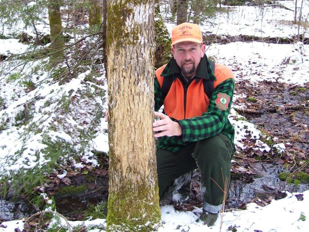 a hunter kneeling behind a deer tree rub