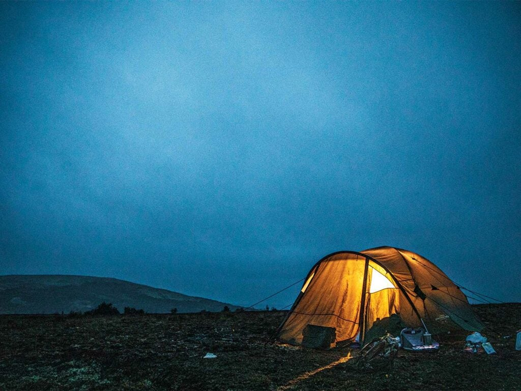 a lit up yellow tent at night in the alaskan wilderness