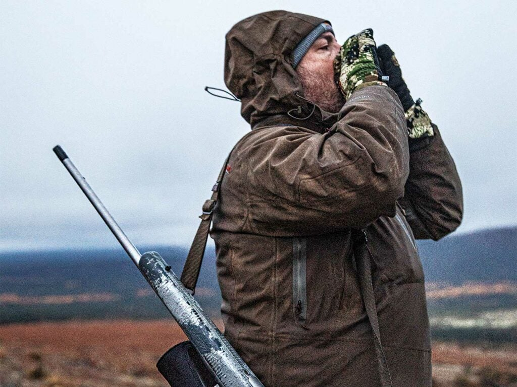 a hunter with a rifle on his back while he bellows out a moose call