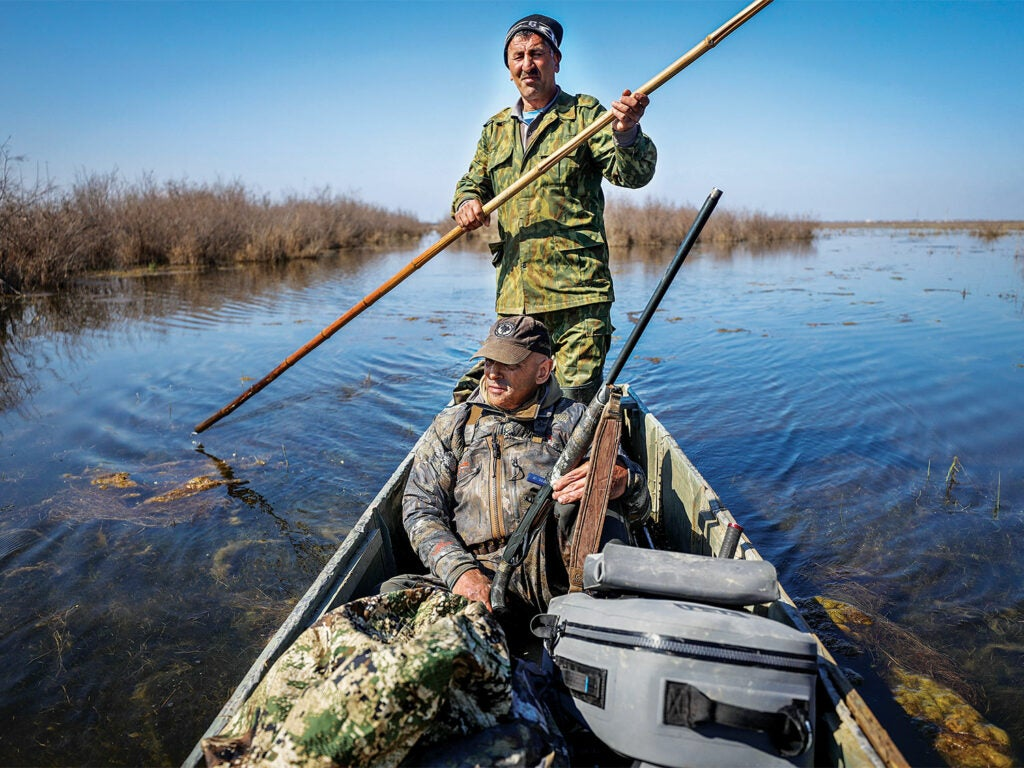 ramsey russell and hunter push-poling through wetlands