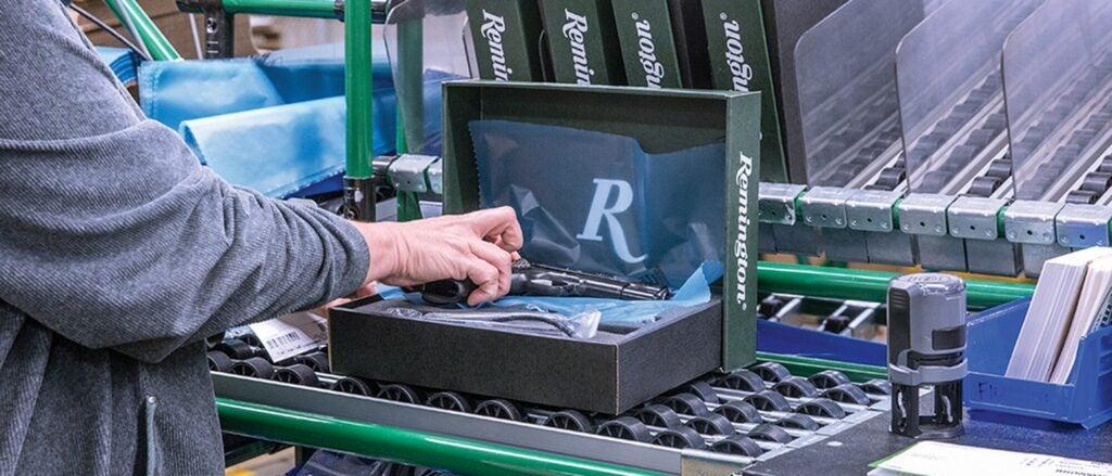 An R-1911 semi-auto handgun is boxed and prepared for shipment