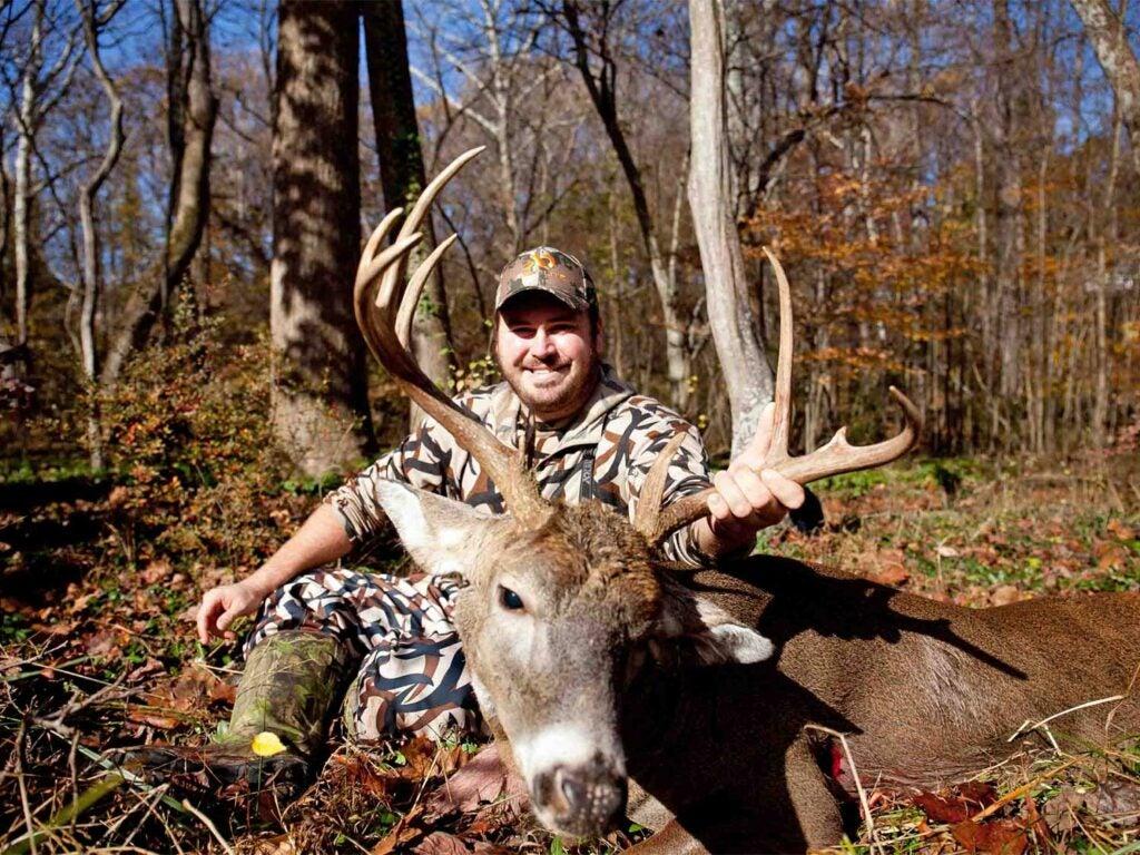 taylor chamberlain kneeling behind a buck