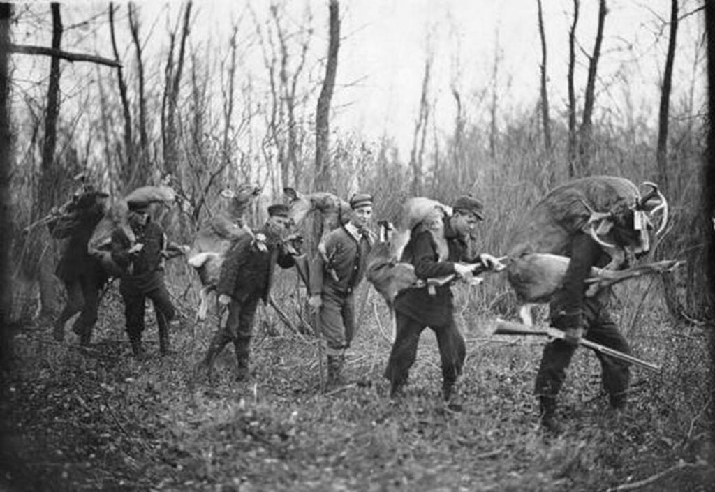 Old-school deer hunters with whitetails slung over their shoulders.