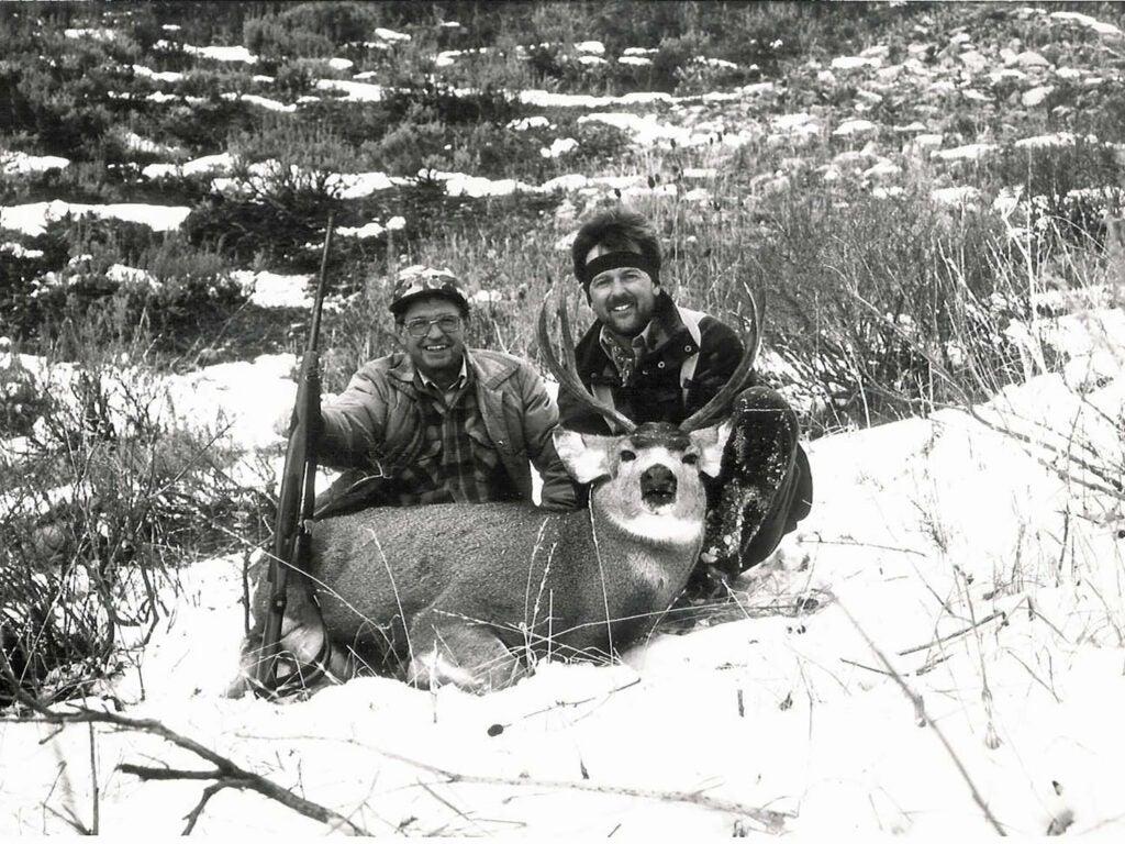 two hunters kneeling behind buck in snow
