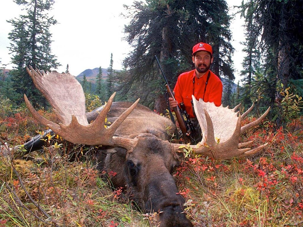 a hunter kneeling behind moose