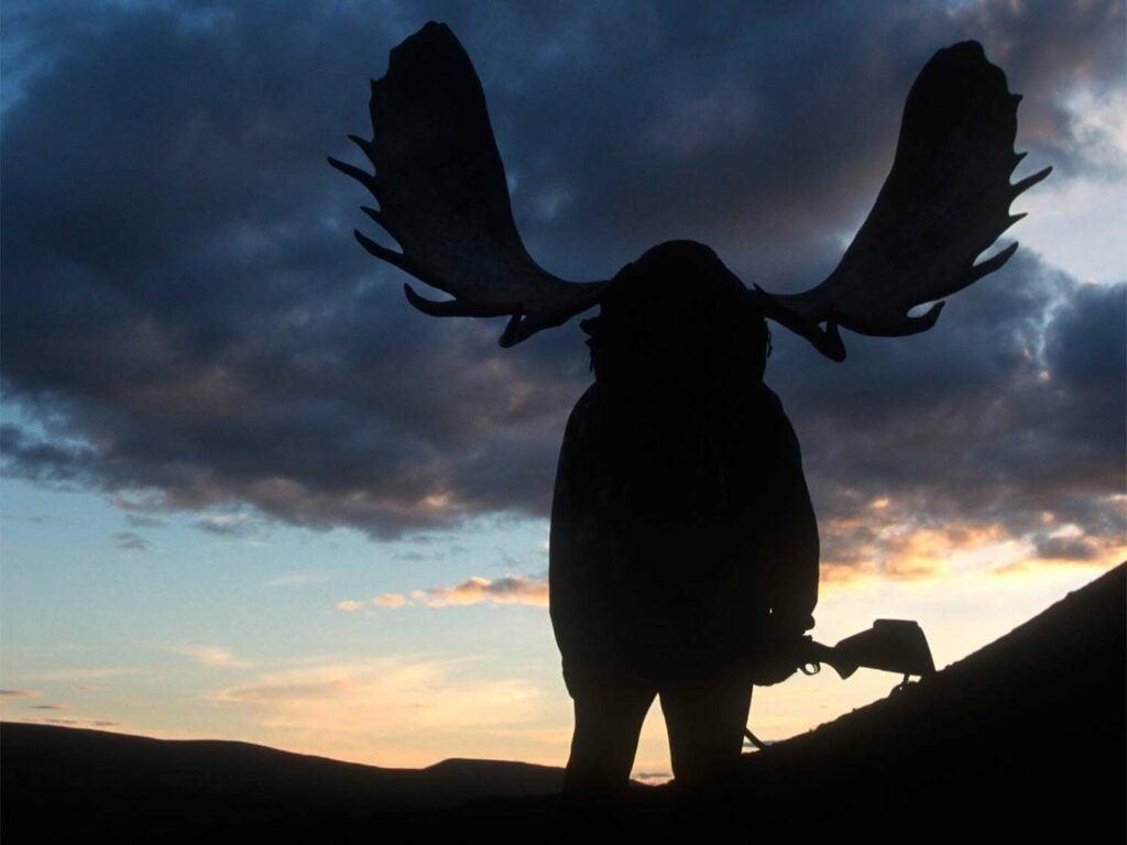 silhouette of a hunter shouldering moose antlers
