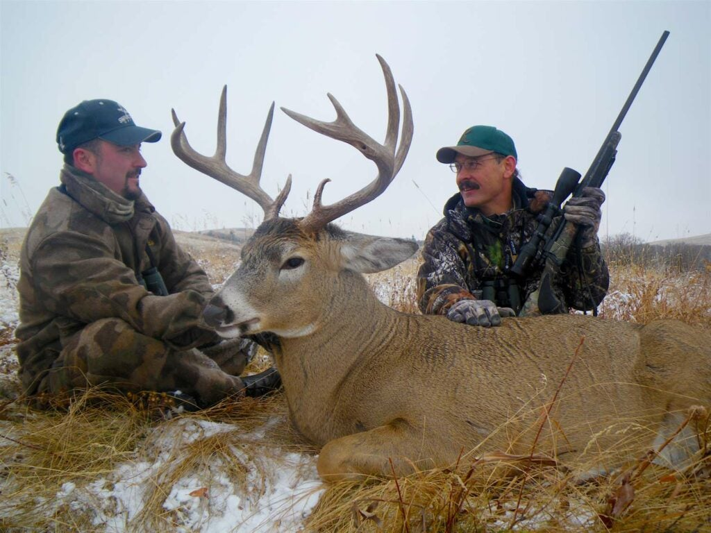 two hunters and a whitetail buck