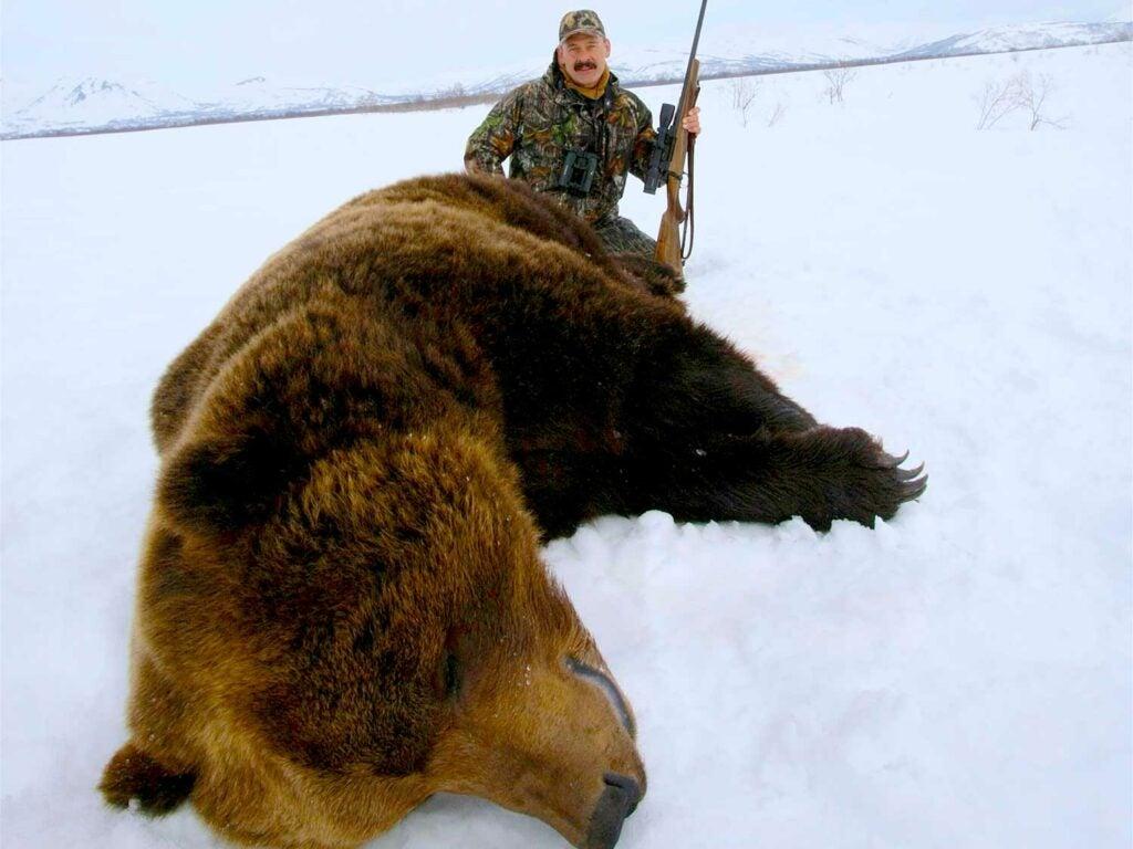 hunter kneeling behind brown bear in the snow