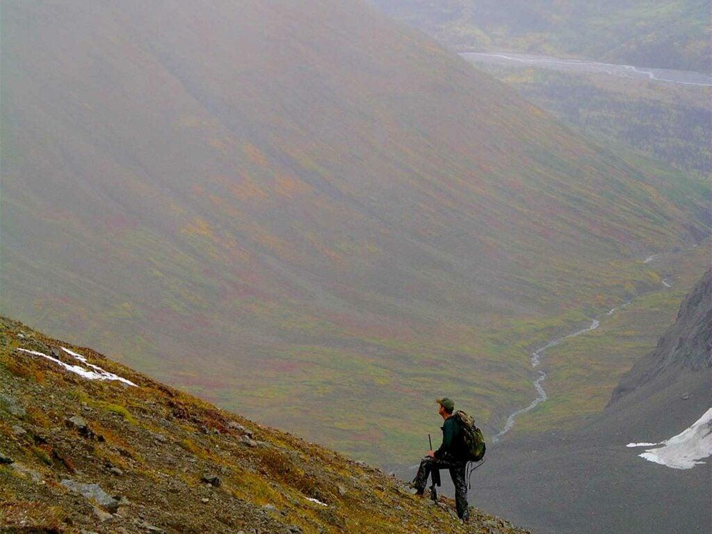 a hunter climbing a mountainside