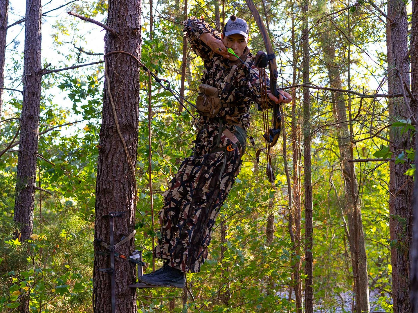 hunter shooting a bow and arrow from a tree saddle stand