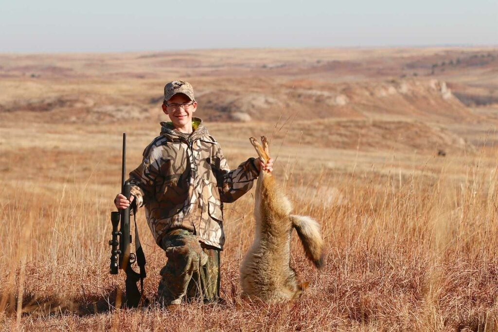 A young hunter with a coyote