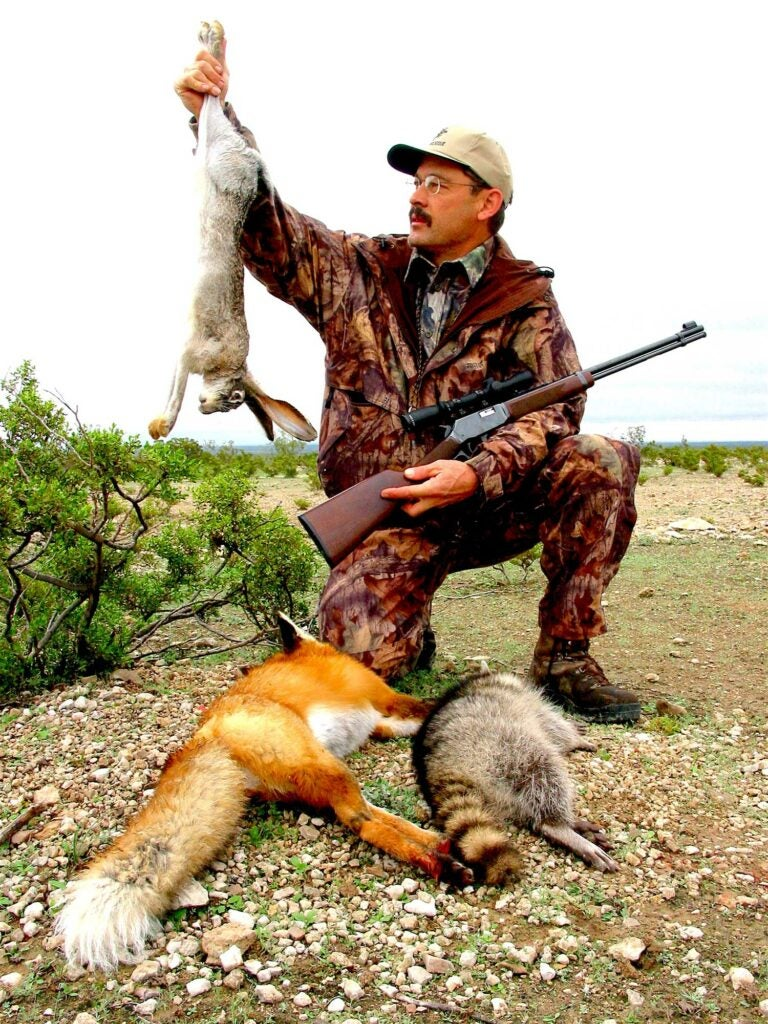 a hunter holding up a small game rabbit