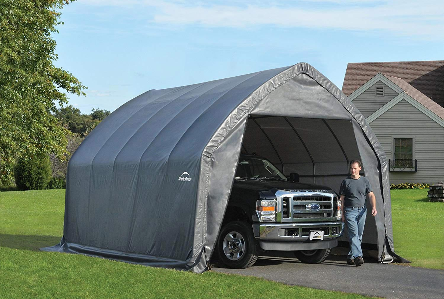 Temporary shed in driveway with truck inside.