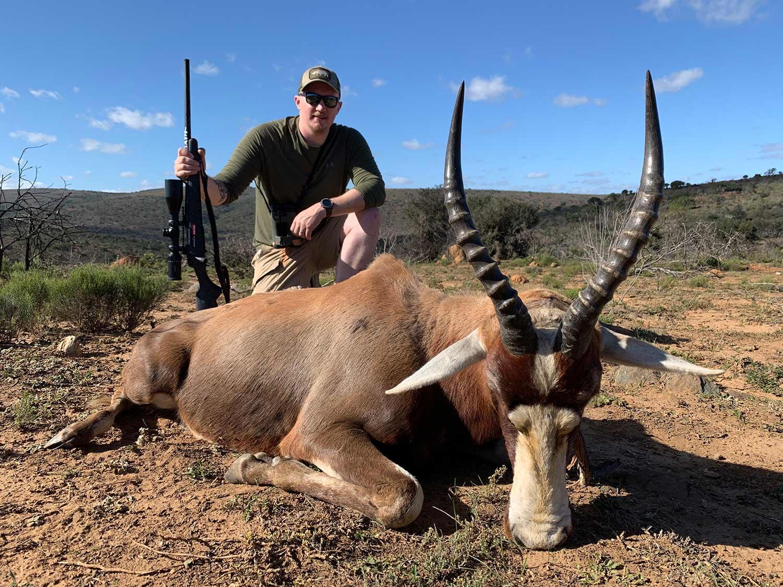 A hunter in africa next to a mature blesbok ram.