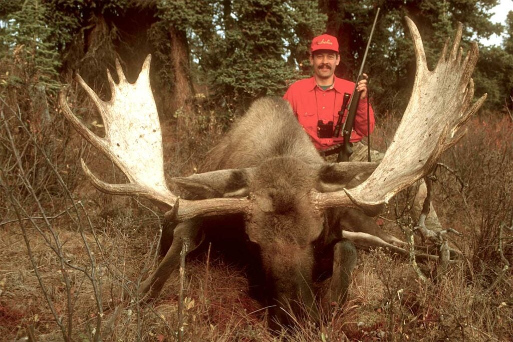 man hunting a large deer in the woods.