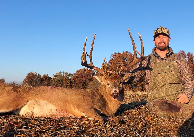 hunter kneeling next to a giant missouri buck.