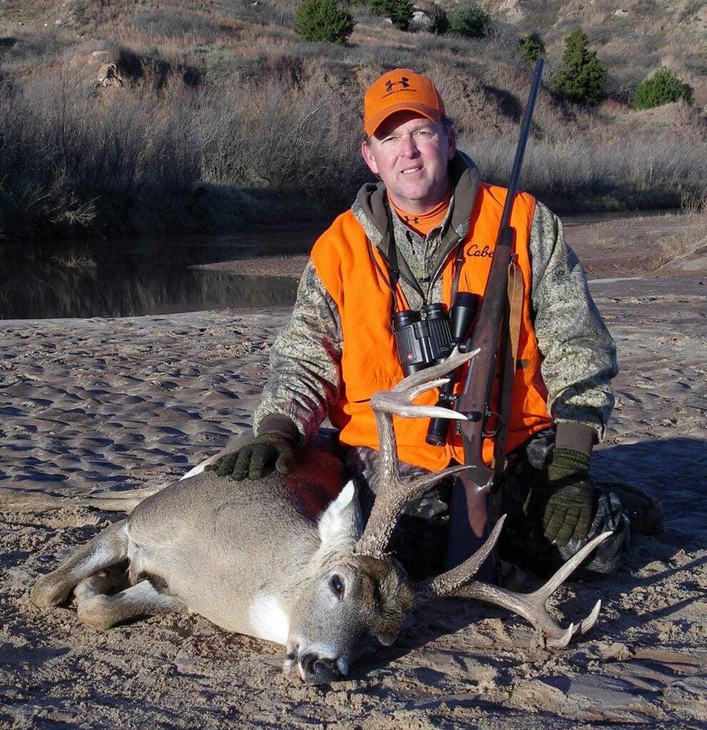 hunter kneeling behind a whitetail buck.