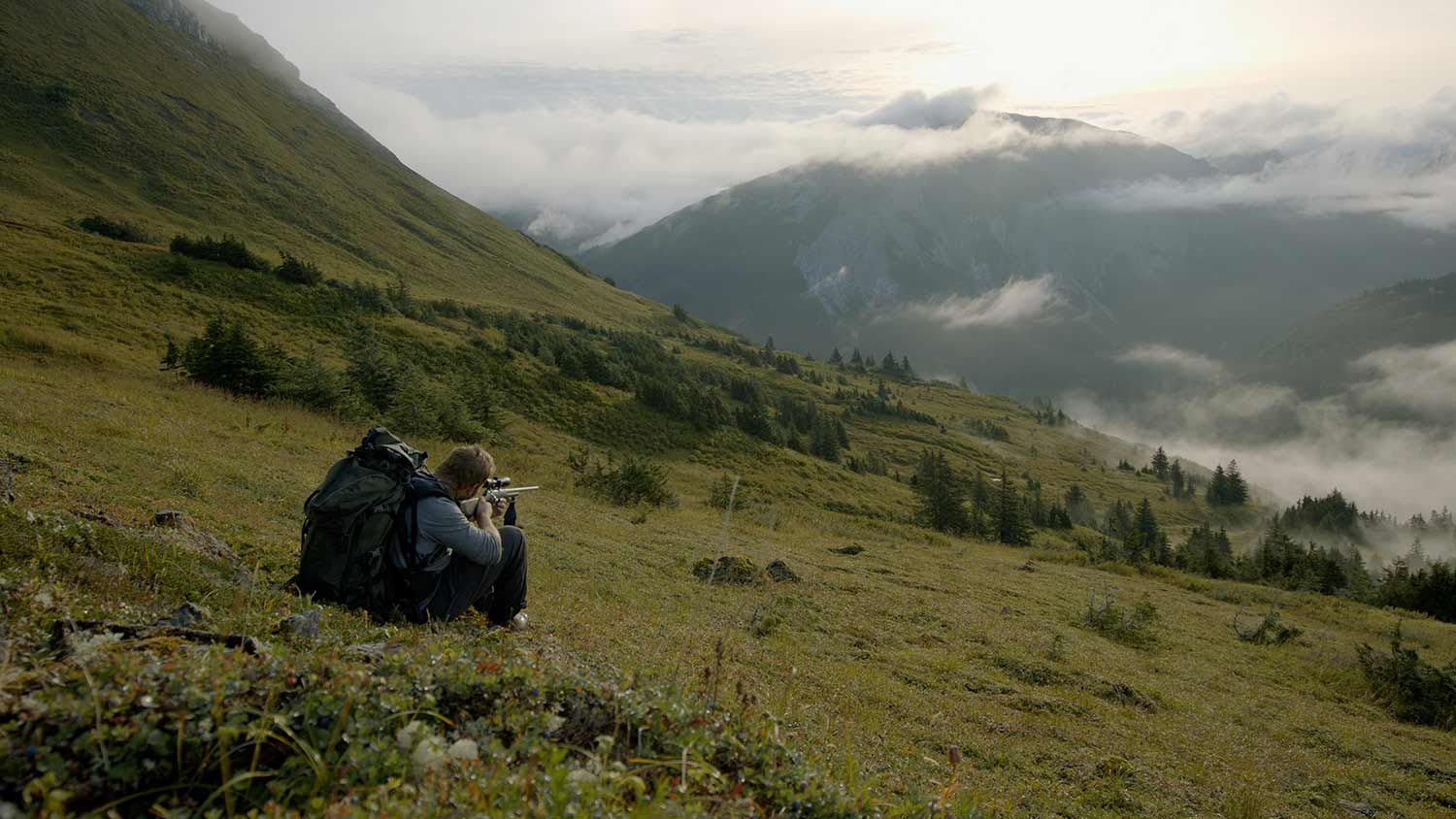 Hunter aiming a rifle in Alaska's Tongass National Forest