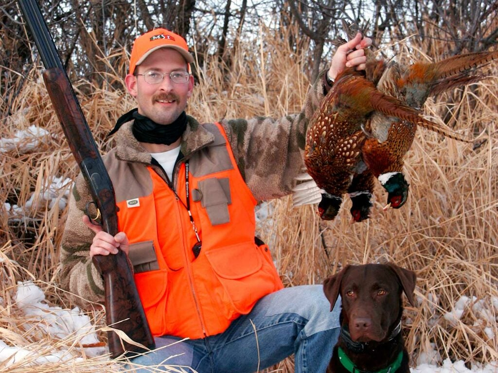 Hunter holding up a pheasant.