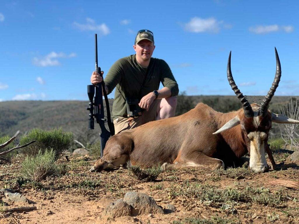Tyler Freel kneeling behind a Blesbok hunted in Africa.