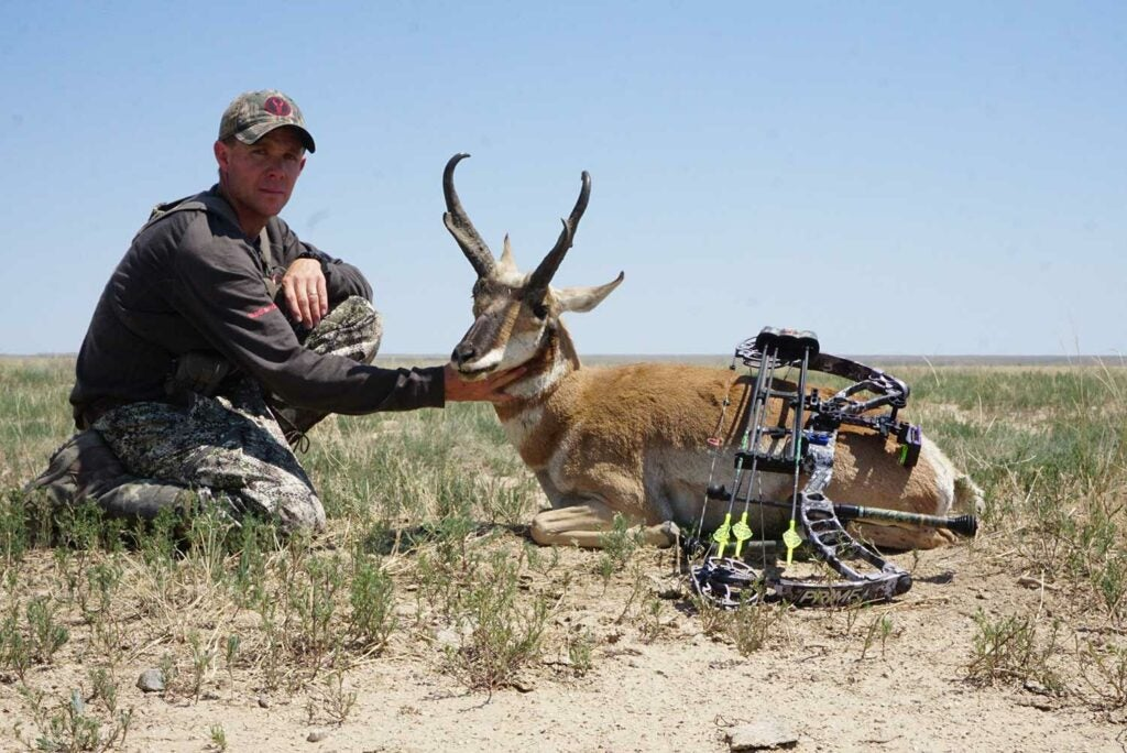A hunter kneeling beside a South Dakota antelope.