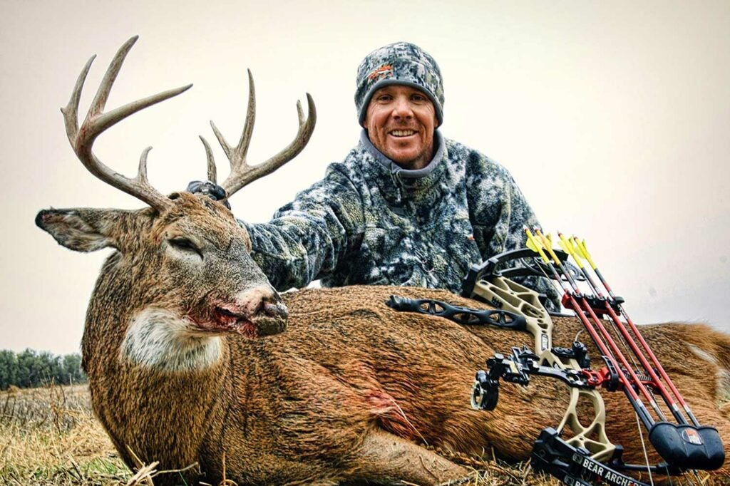 A hunter kneeling behind a Kansas buck.