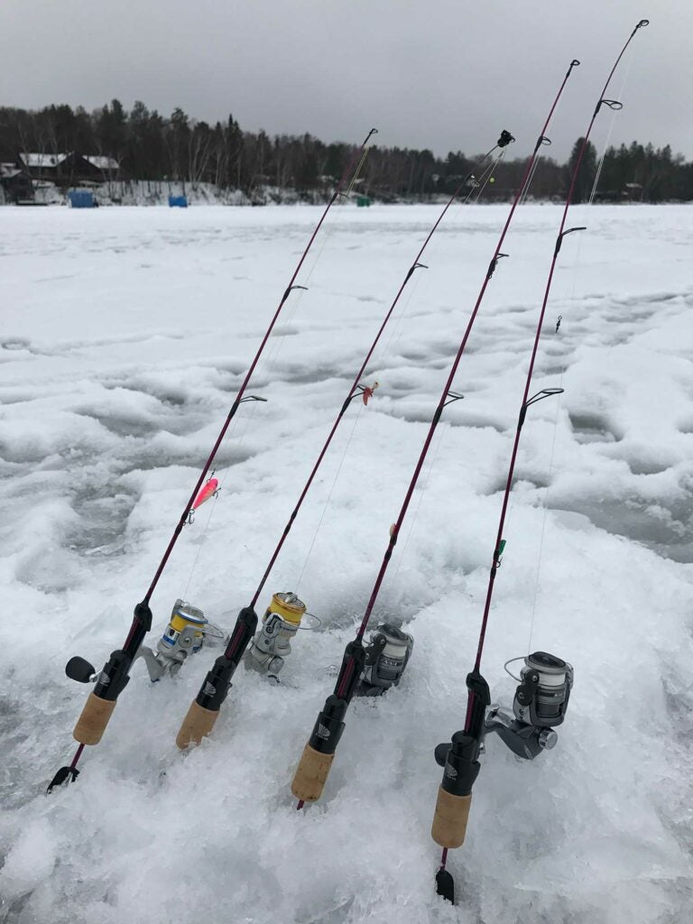 four fishing rods in the snow.