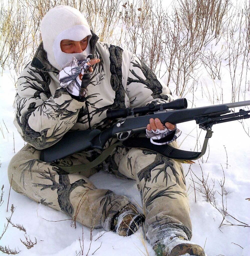 A hunter sitting in the snow.
