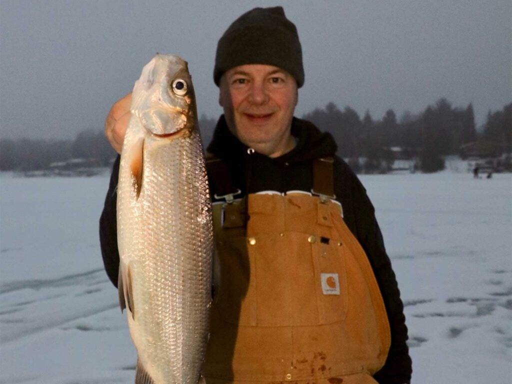 Angler holding up whitefish.