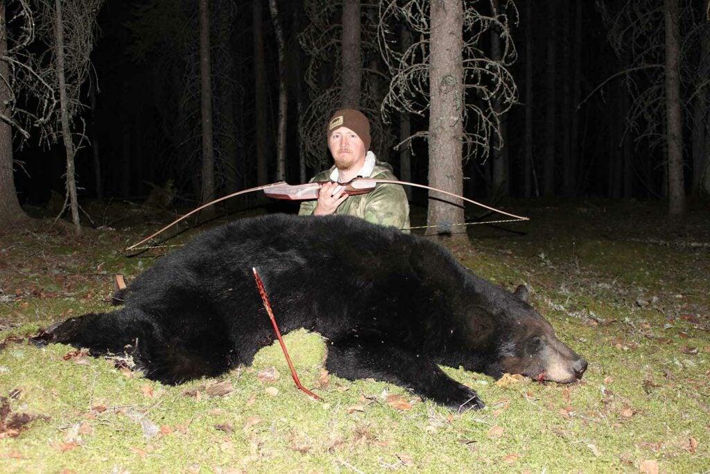Tyler Freel kneeling behind a black bear.