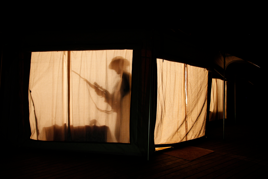 Silhouette shadow cast on the interior cloth wall of an African safari tent.