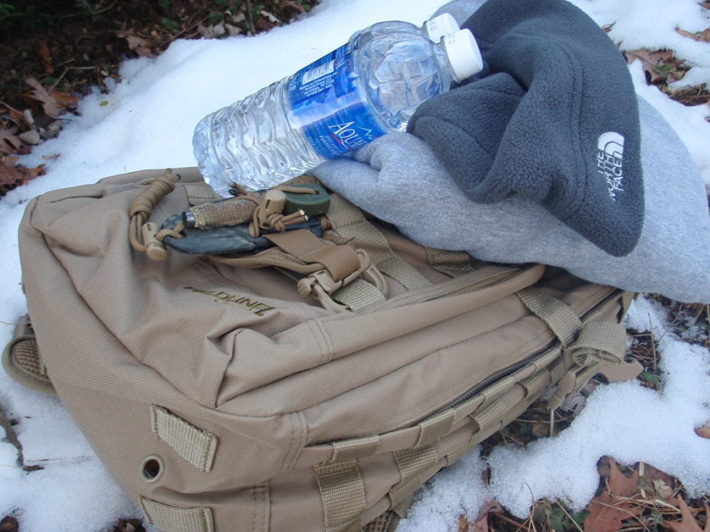 winter survival gear and water in the snow.