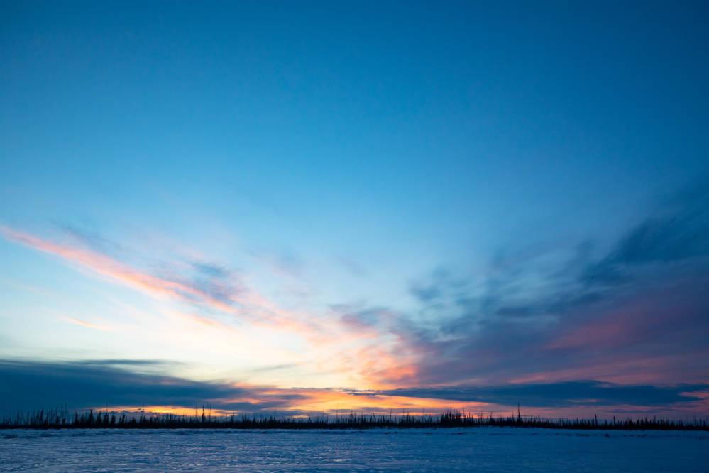 landscape of sun shining over a frozen lake.