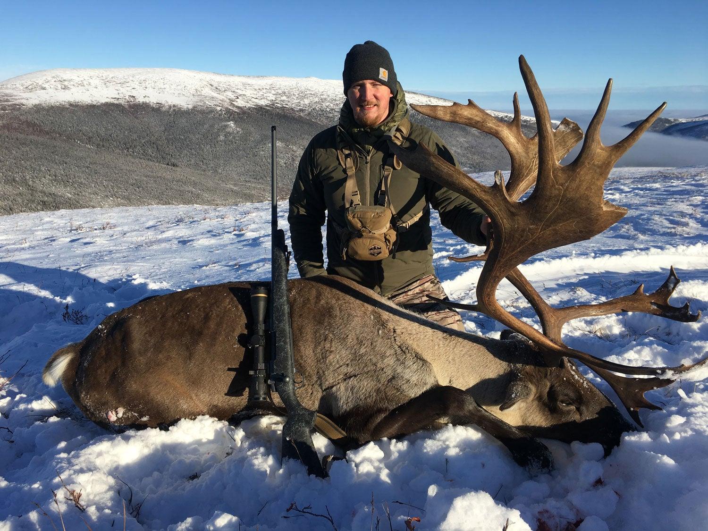 Tyler Freel kneeling behind caribou in snow.