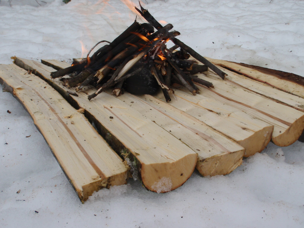 A fire built on planks of wood to keep dry from the snow.