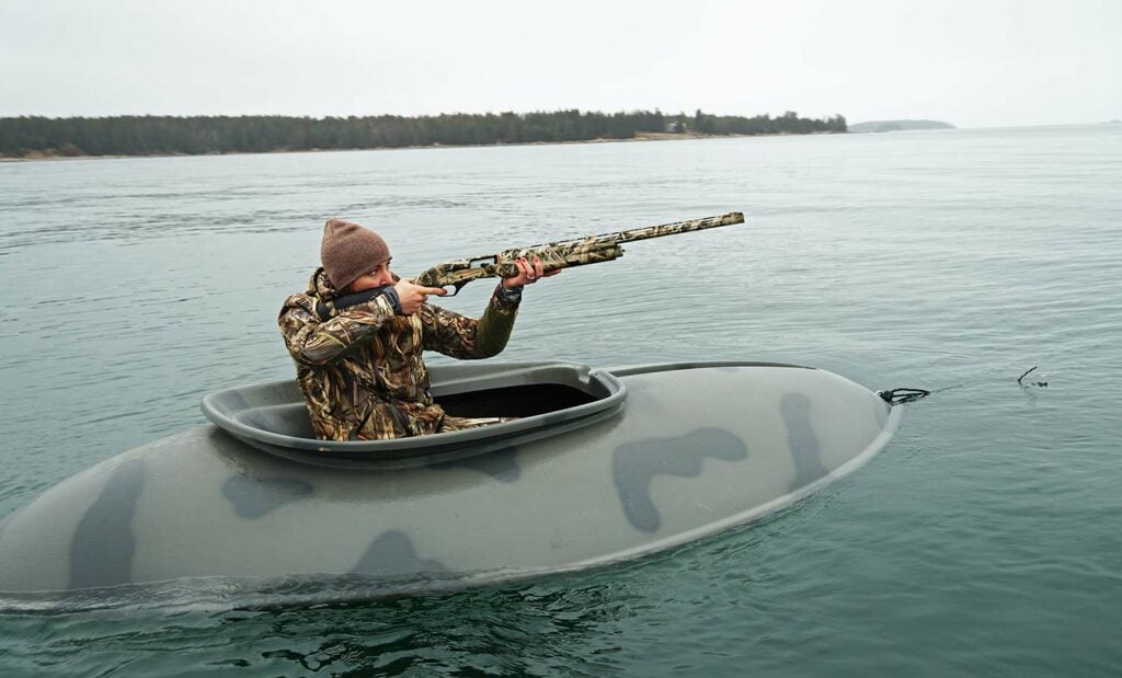 Hunter in a hunting boat hunting waterfowl.