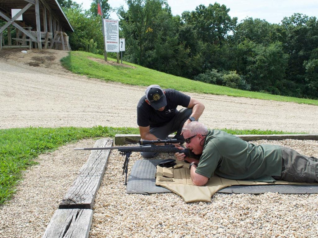 Two men checking scopes on a rifle.