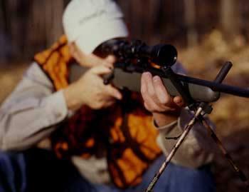 A hunter aiming a rifle using shooting sticks.
