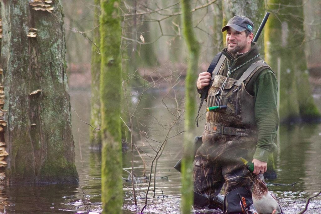 A hunter wading through flooded timber while duck hunting.