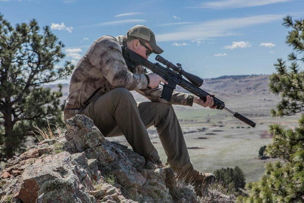 hunter firing a rifle with a muzzle suppressor.