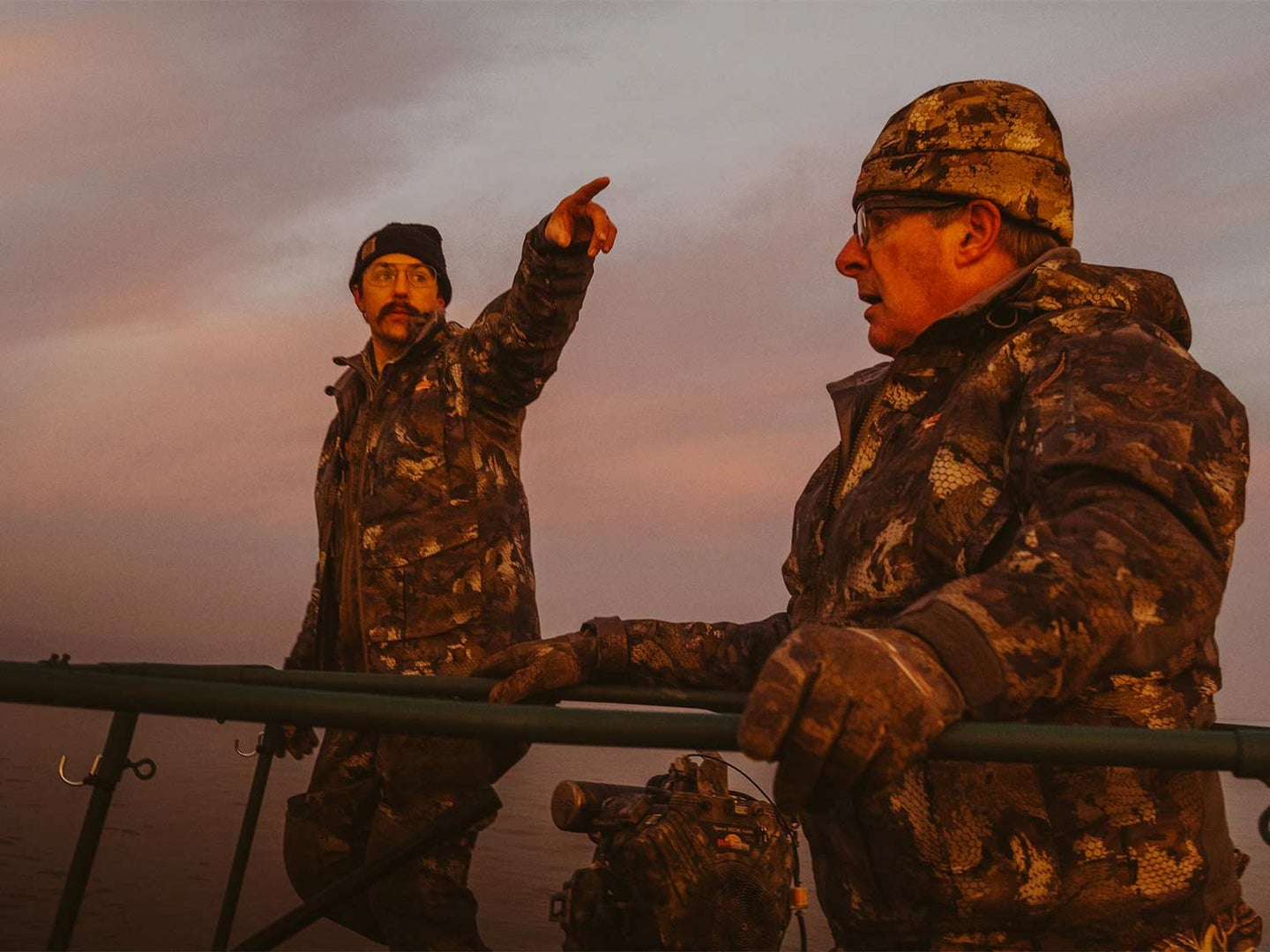 Two male hunters in a field at sunset.
