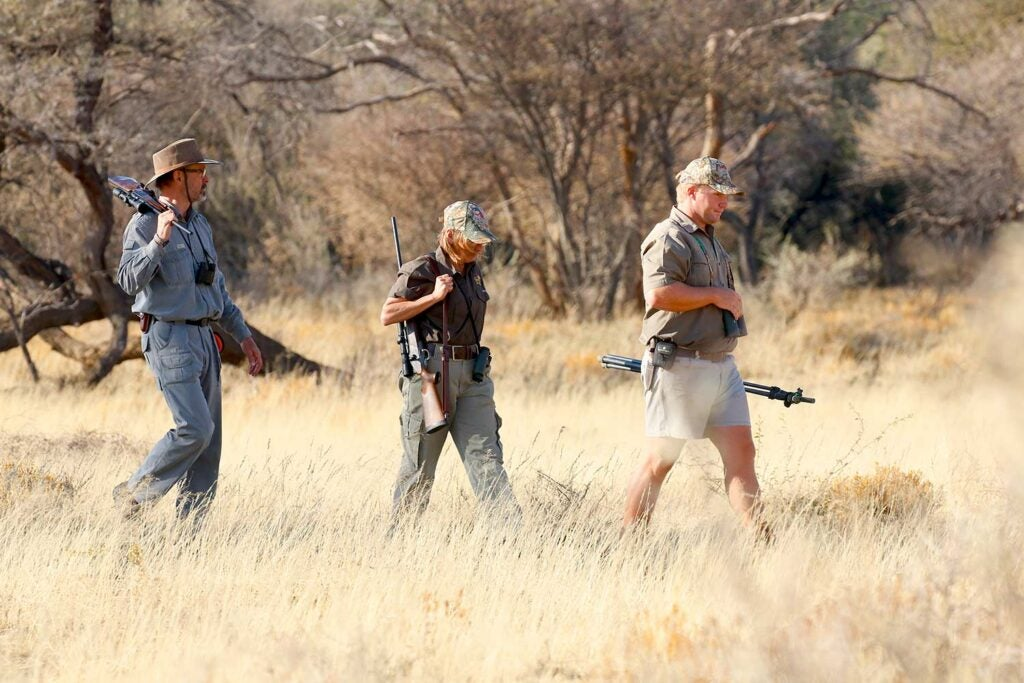 Hunters walking through the fields in Africa.