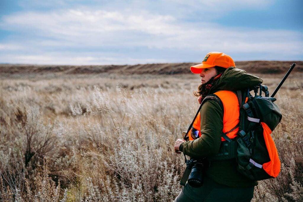 Female hunter in a field.
