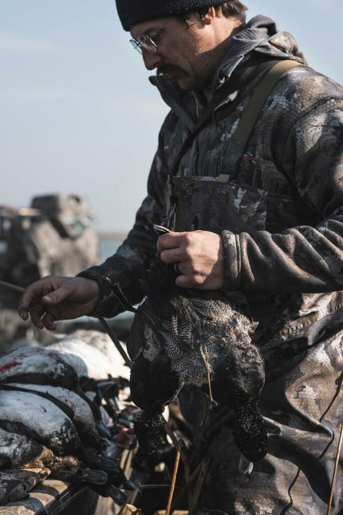 Hunter in a field holding a duck.