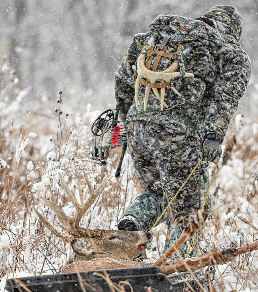 A bowhunter sleds out a heavy central Kansas whitetail, taken during a snowstorm.