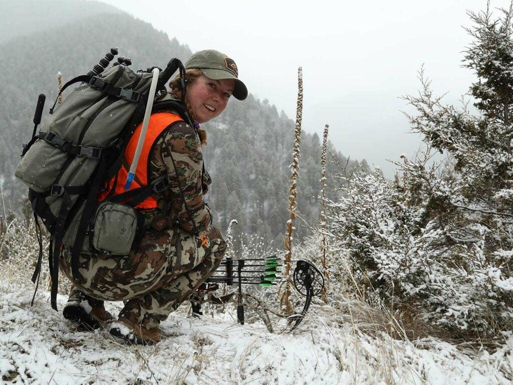 Female hunter kneeling in the snow.
