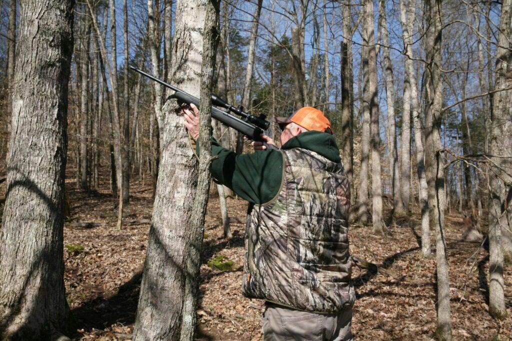 Hunter shooting at a squirrel.