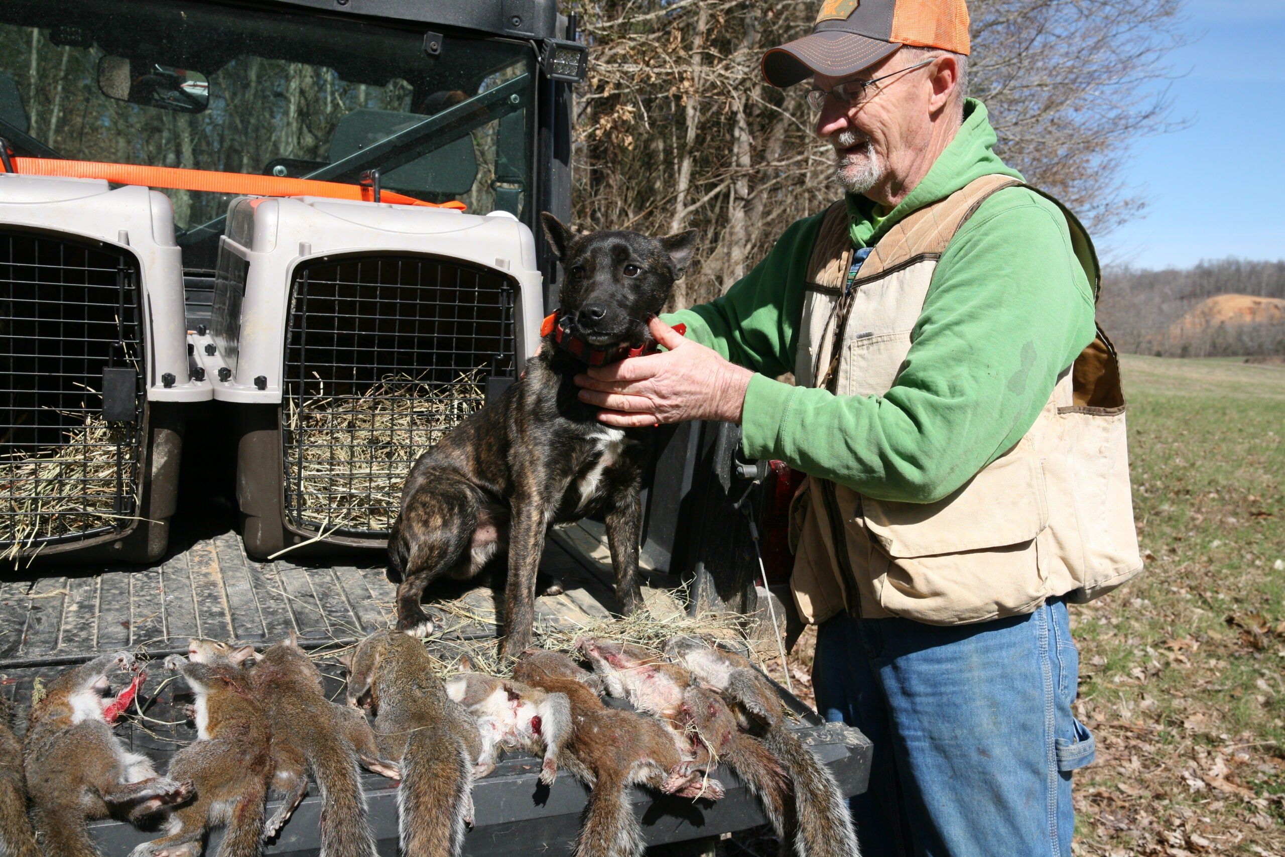 Hunter with dog and dead squirrels on the back of truck.