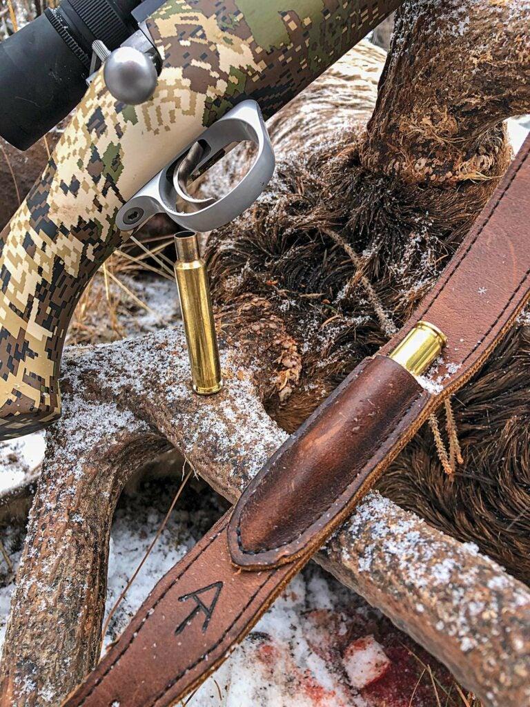 A spent .280 Ackley Improved shell beside von Benedikt's homemade rifle sling.