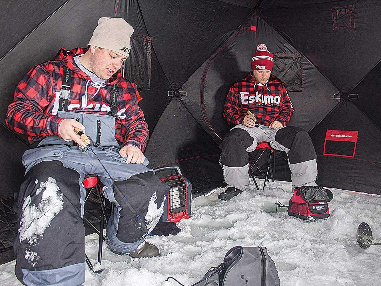 Fishermen sitting in ice fishing shelter.